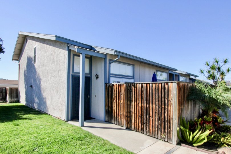1 story duplex/complex with a fence on a sunny day.