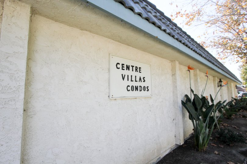 Placard sign for Centre Villas Condos in Chula Vista, CA. Birds of paradise growing alongside.