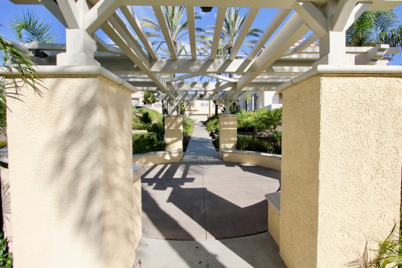 A white wooden pergola casts a shadow on a patio at Gold Rush condos