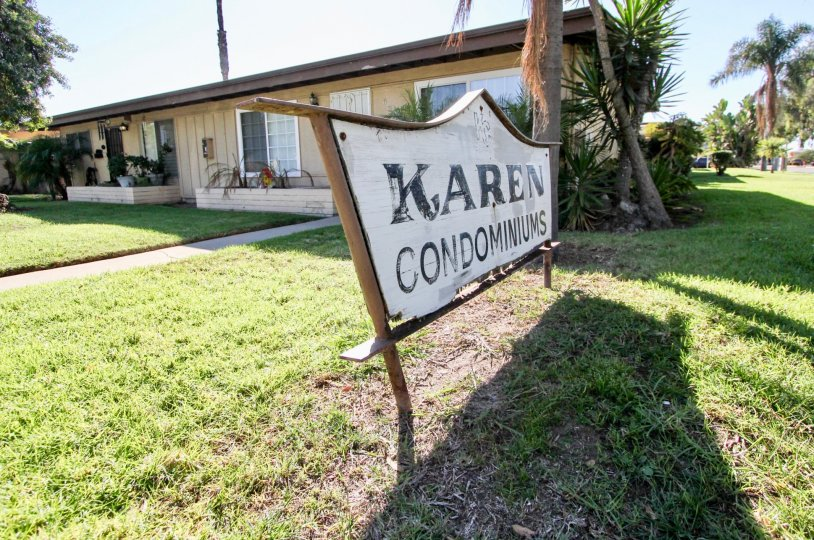 A white and wooden sign announces to visitors they have arrived at the Karen Condominums