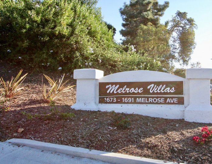 a sign of Melrose Villas welcoming people right in with trees and greenery all around