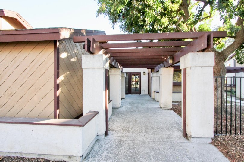 Photo of a paved back walkway to a white and brown building in Melrose Villas community of Chula Vista, California.