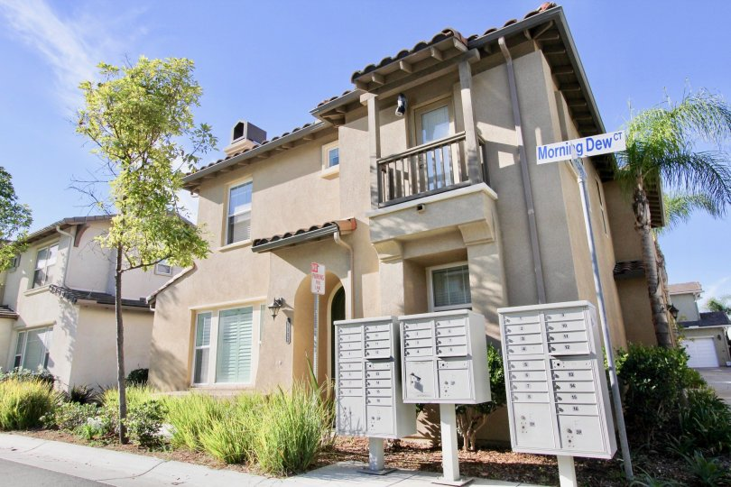 2 story house with small balcony, mailboxes, trees, and small bushes on a sunny day.