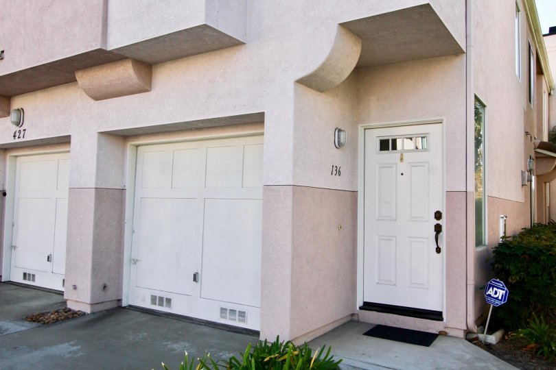 The outside of a Sanibelle home showing the side of the building and two garage doors as well as the entrance to 734 in Chula Vista