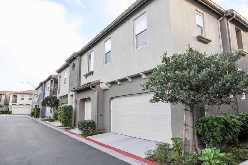 A clear road in front to the garages and front doors of the tidy and peaceful townhomes of Summer Hill in Chula Vista, California.