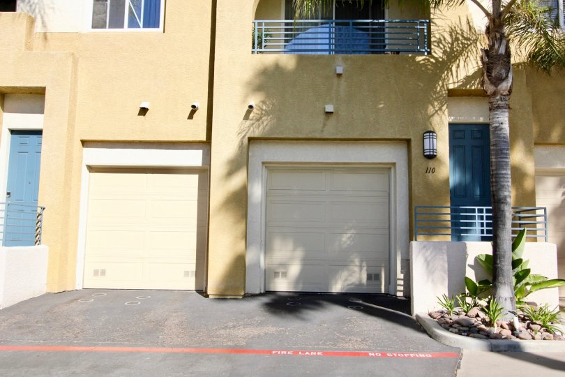 A sunny day in the area of Villagio, outside, garages, palm tree, balcony, driveway, shadows