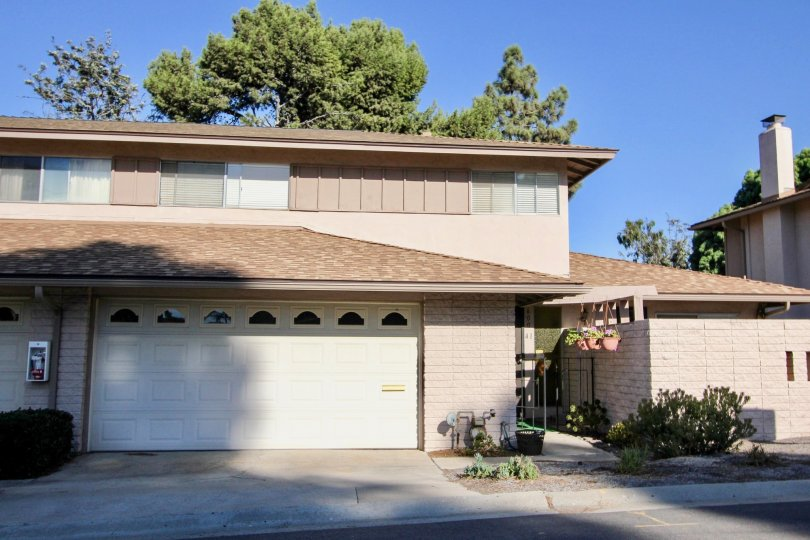 A sunny day in the area of Windsor Heights, outside, garage, entrance, plats, gas meter, trees