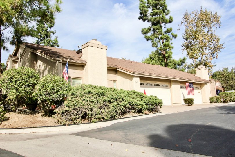 Garage view with American flags and bushes at Windsor View in Chula Vista, California
