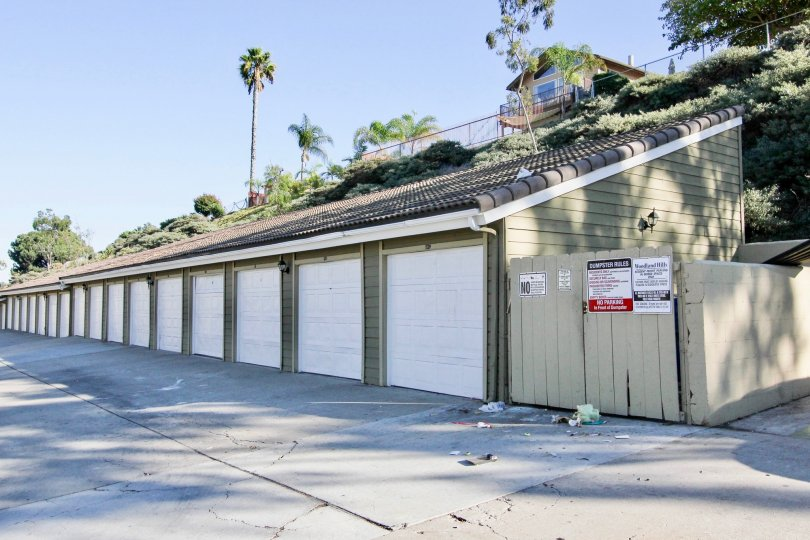 Single car garage units with imposing sloped roof adjacent to garbage disposal shed at Woodland Hills