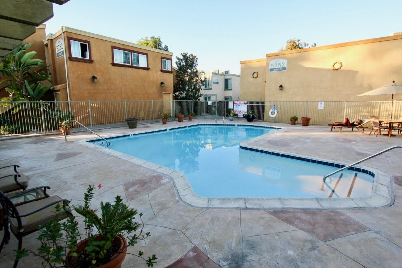 A public pool in a Clairemont Mesa California apartment complex. Patio furniture and potted plants are present.