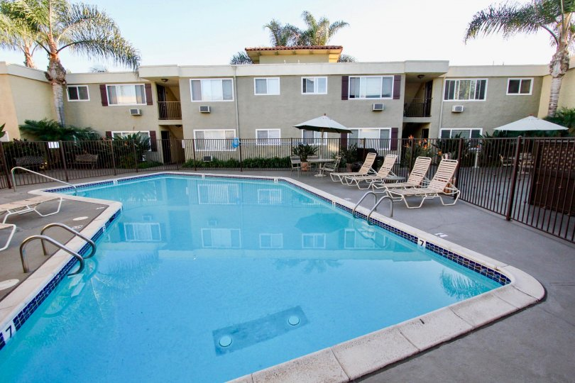 Large blue swimming pool and seating area below residential building at Heritage Park East in Clairemont Mesa California