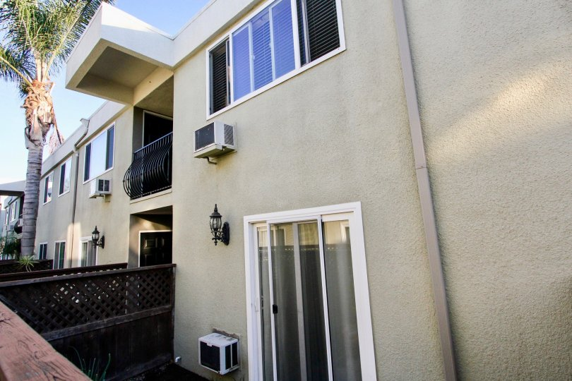 Off white unit with wall air conditioner units and balconies at Heritage Park West of Clairemont Mesa, California