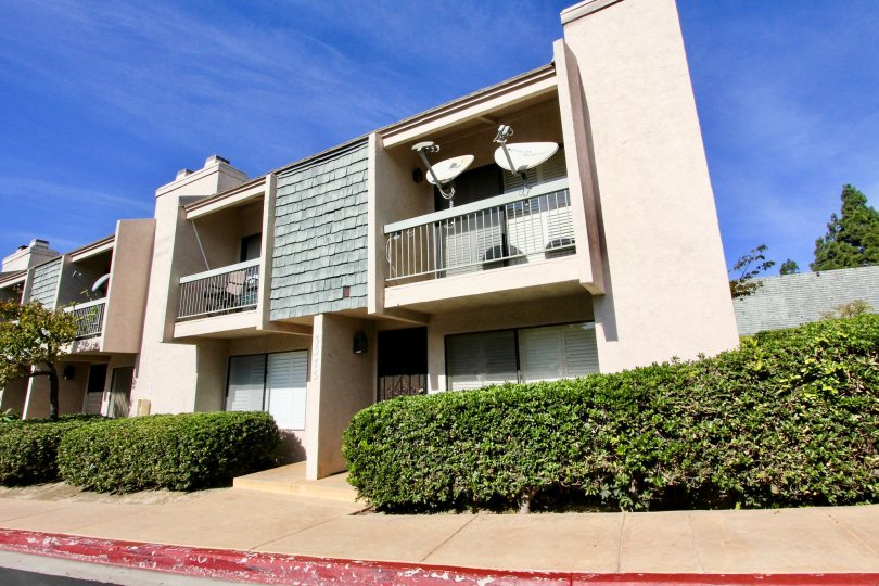 2 satellite dishes are attached to the railing on the balcony at the Pacific Racquet Club community in Clairemont Mesa California.