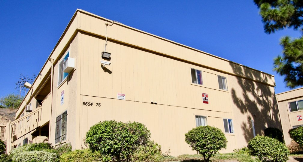 Two story residential unit surrounded by plants at Mesa Greens in College Area California