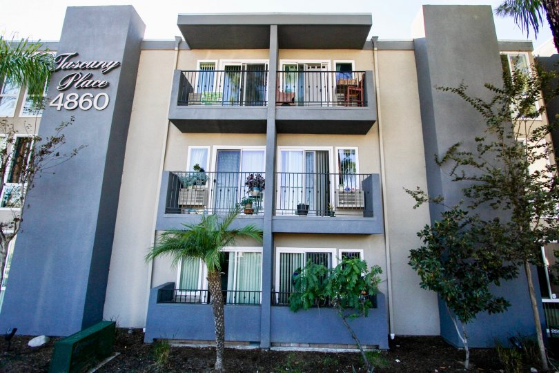 Three story residential building with trees at Tuscany Place in College Area California