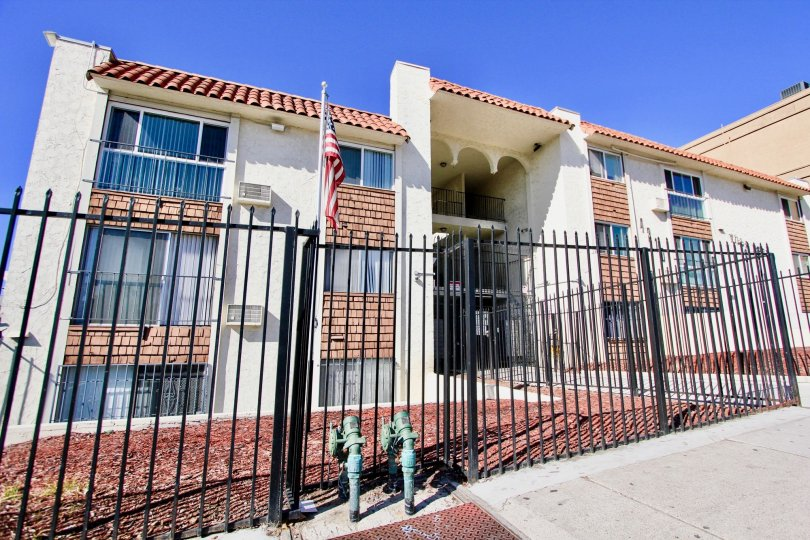 Three story housing units behind a black iron fence at Villa Madrid in College Area California