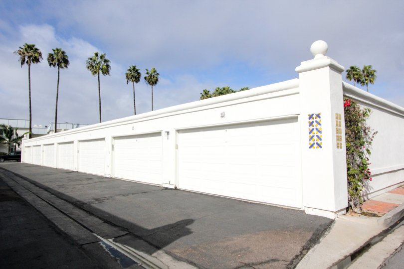 A row of white garage doors with some palm trees in the background during a sunny day in Antigua Court, Coronado, CA