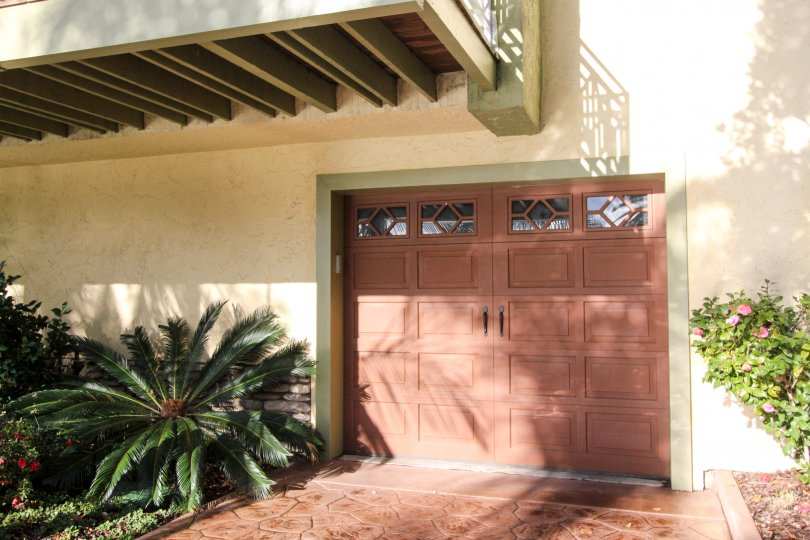 A garage door in a home in the Cayman Cove community of Coronado, California, dappled with sun and shade.