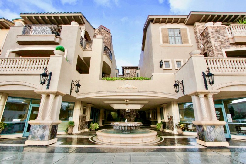 A luxurious apartment building with a fountain during a sunny day in Regatta Bay, Coronado, CA