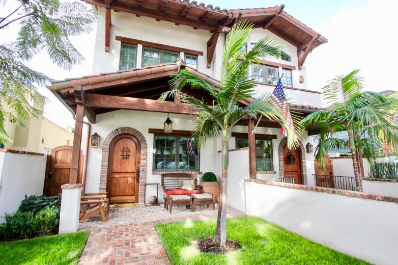 An intricate style home with palm trees in the front in the community Villas.