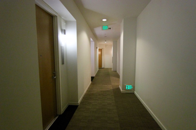 A hallway with exit signs and several doorways with lighting accents at 350 West Ash