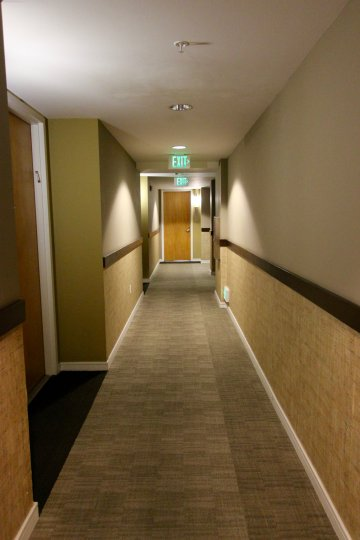 Main access hallway of 350 West Ash community with ceiling sprinklers and standard exits