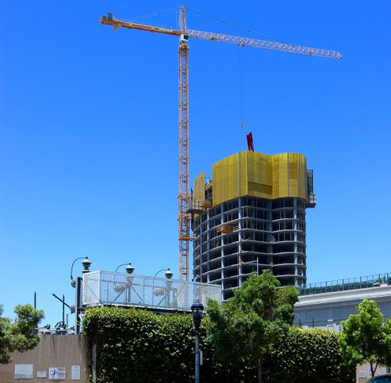 A tall crane being used in the constructions of a building in Pacific Gate on a beautiful day.