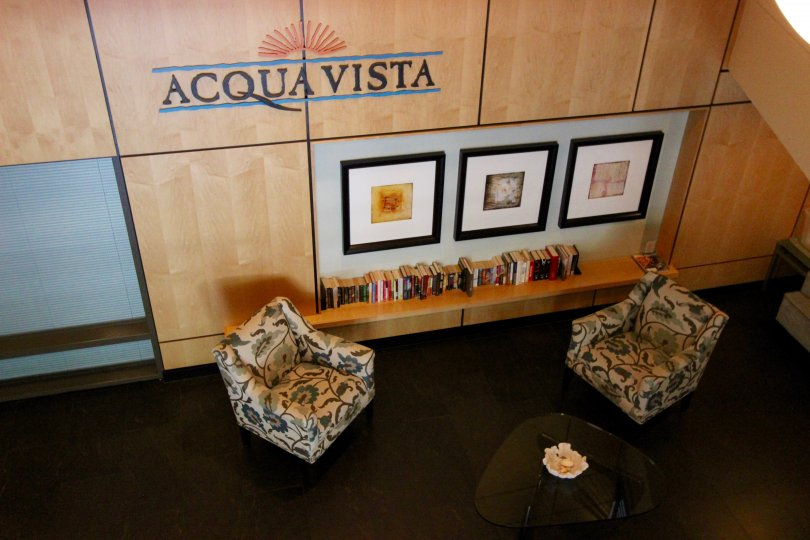 Two chairs and framed pictures under community sign at Acqua Vista in Downtown San Diego CA