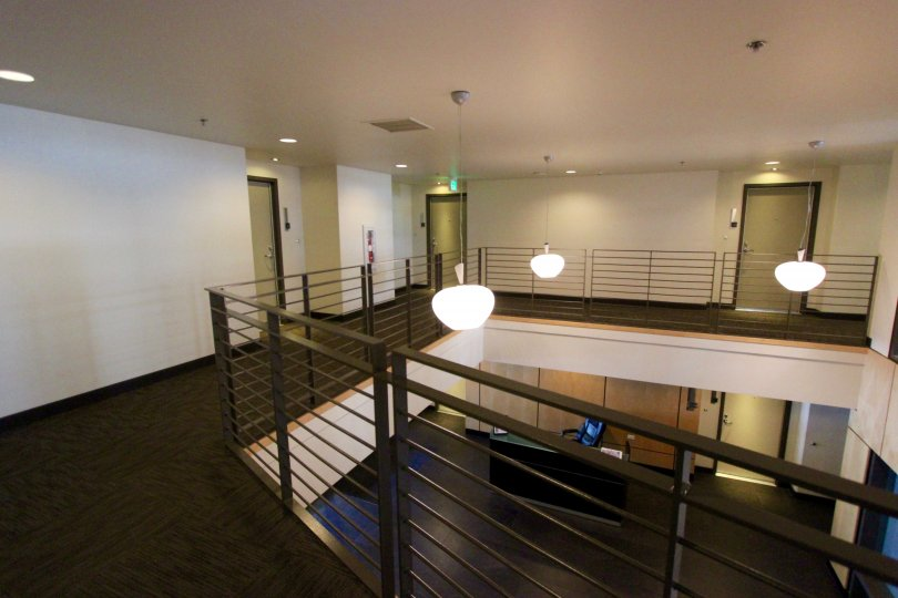 A lobby as viewed from an upstairs balcony complete with modern decorative lighting