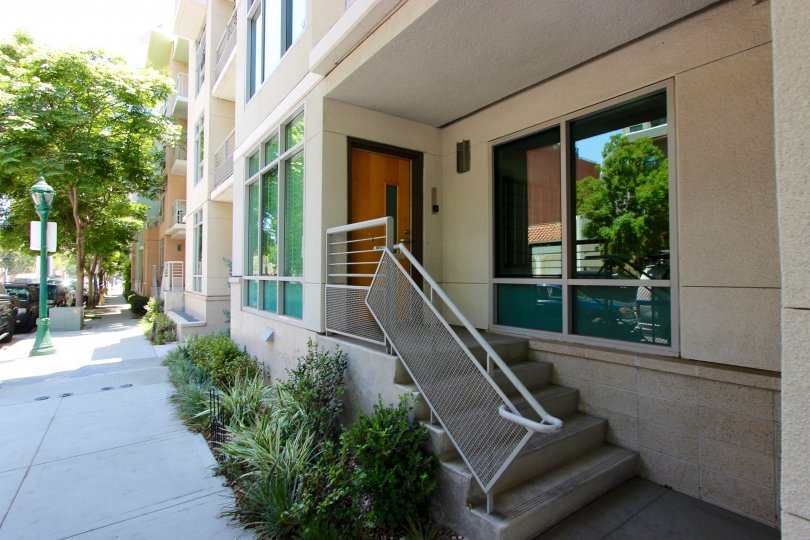 A view of the exterior steps and front door of the Acqua Vista office building on a shady street.
