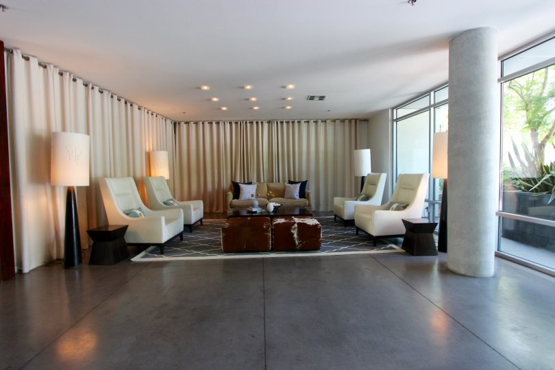 Modern living room with concrete pillars and flooring and large bay windows in the community of Aloft, San Diego, CA