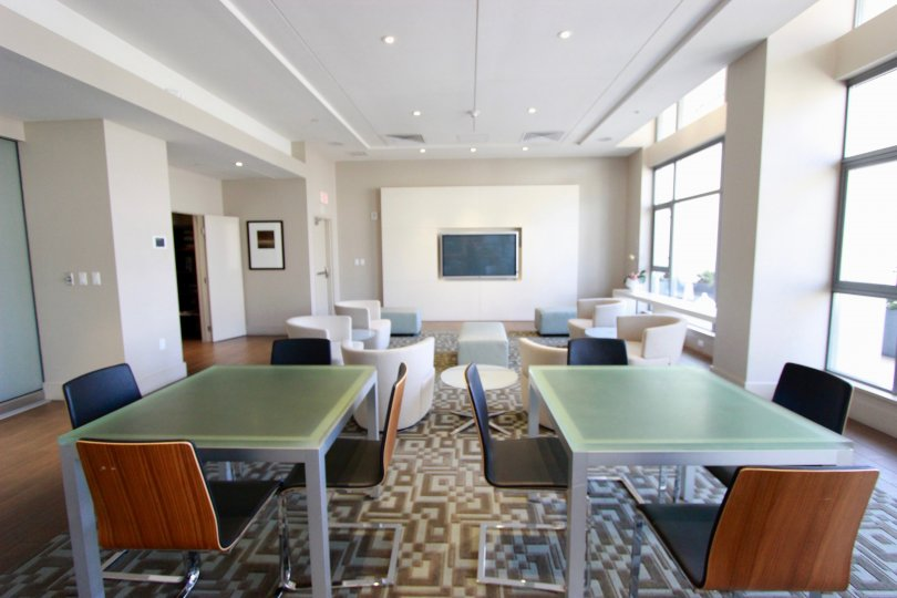 Welcoming common area with tables, chairs, and television in Alta.