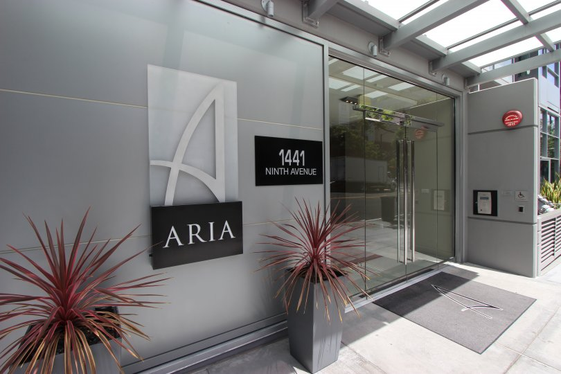 The entry doors to Aria with welcoming plants and signage.