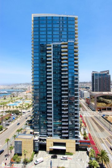 Tall condo high rise with blue glass windows at the Bayside in Down downtown San Diego CA