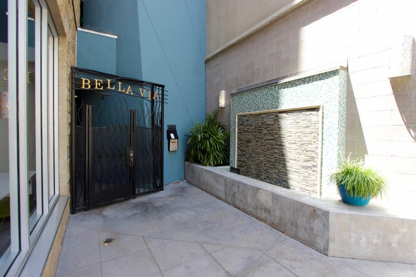 The exterior of the modern Bella Via buiilding including artistic tile work and potted plants and private entrance.
