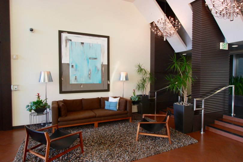 An interior view a community area in the Breeza building with retro furniture and framed modern painting.