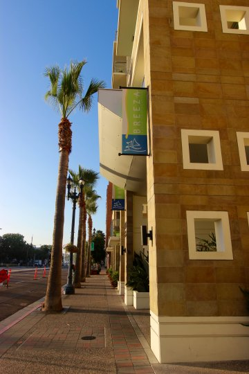A sunny day in Downtown San Diego's Breeza Community. A sidewalk with trees and an Apartment building.
