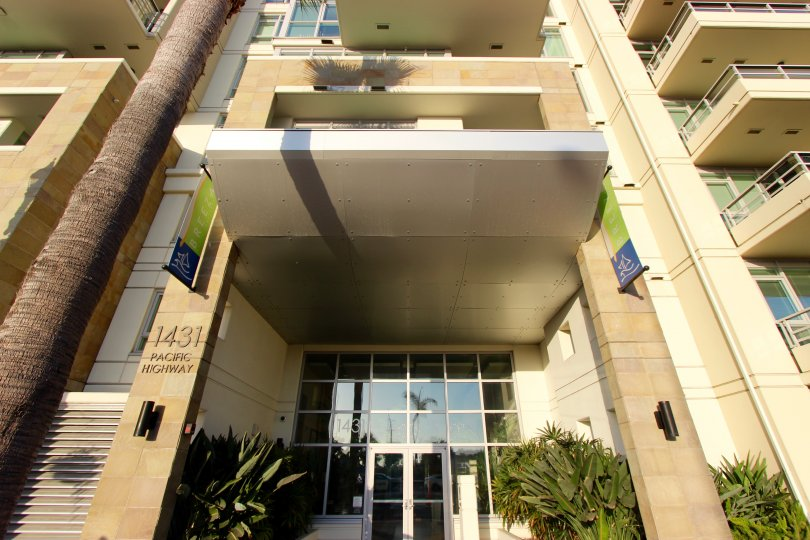Sidewalk camera view angled up of the Brezza Condos Downtown San Diego California landescapeat front door of small palms