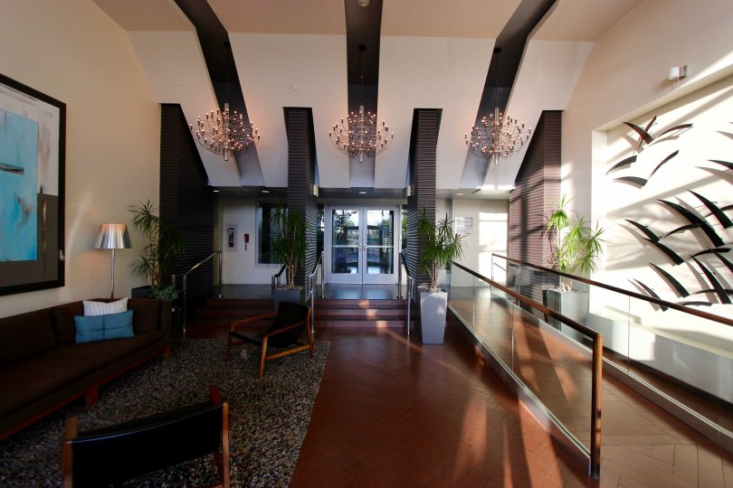 A sunny room in the Breeza community of downtown San Diego, California with three chandeliers
