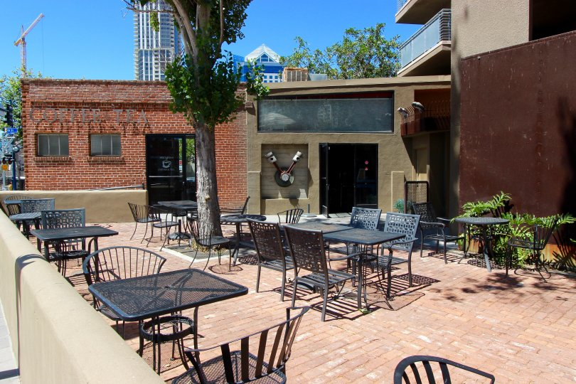 A brick dech with tables and chairs in the Brickyard community in downtown San Diego, CA