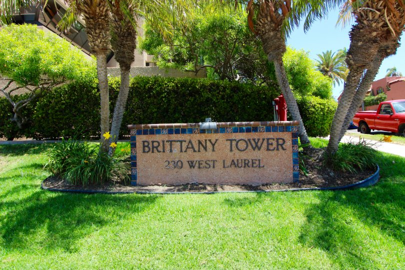 Brown and blue stone sign between two palms inside Brittany Tower at Downtown San Diego CA