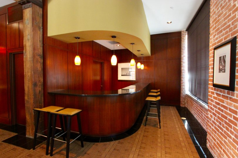Located in the Cityfront Terrace community of Downtown San Diego, California, this bar is full of character and warmth. The contrasting textures of the dark wood paneling, red brick, and parquet floors bring a ton of life to this small space.