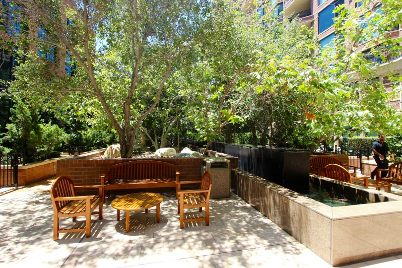 A sunny day at Cityfront Terrace in Downtown San Diego with outdoor seating, beautiful foliage and water features.