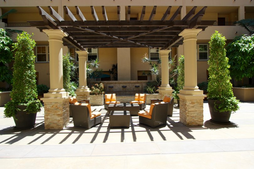 Orange and brown patio furniture sits under a pergola at Citywalk condos