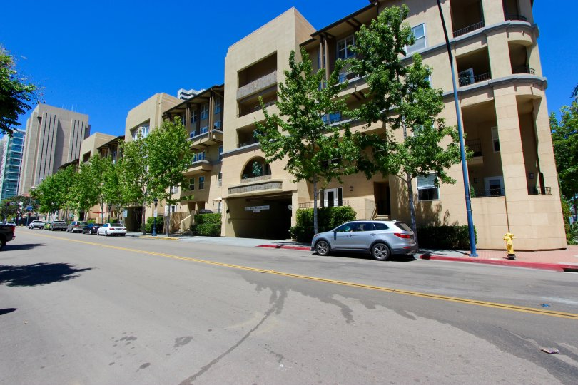 The exterior of a block of buildings along the street in the Citywalk community with shade trees.