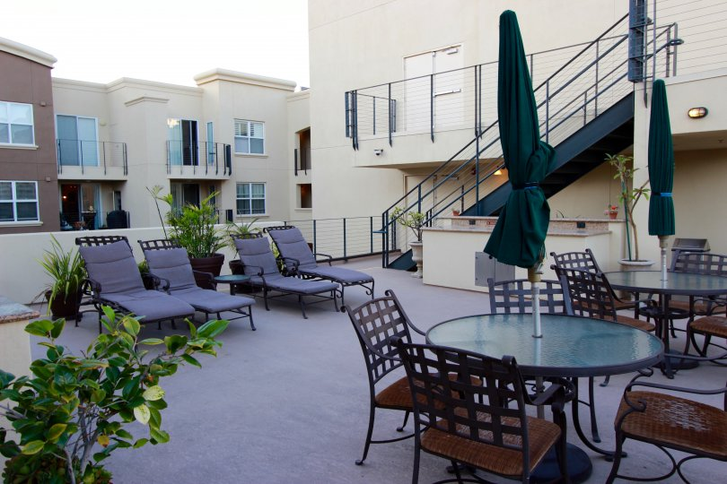 A view of the outdoor terrace dining area, staircase, and balconies at the Crown Bay apartment complex on a sunny afternoon.