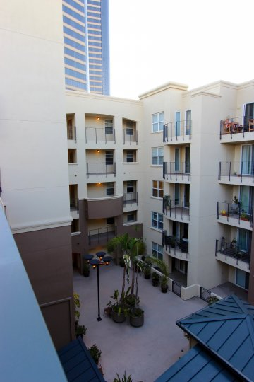 View of the courtyard of the Crown Bay Condos Downtown San Diego California with lighted lampost and potted palm trees in middle