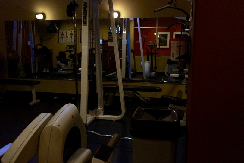 Dimmly lit picture of Work out room of Crown Bay. Mirror reflecting back of room.