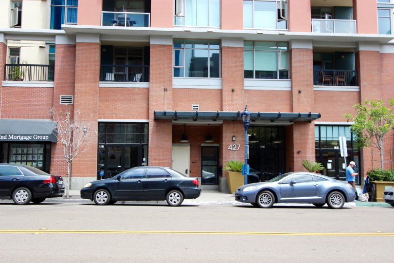 Cars parked below a tall red brick building at Diamond Terrace in Downtown San Diego CA