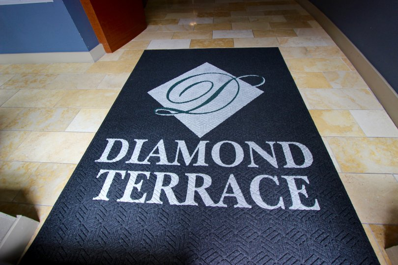 Large black mat with gray writing and shapes inside Diamond Terrace at Downtown San Diego